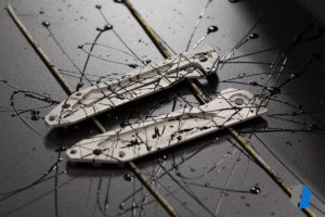 Titanium knife scales splashed with nail polish to create a mask ahead of anodising.